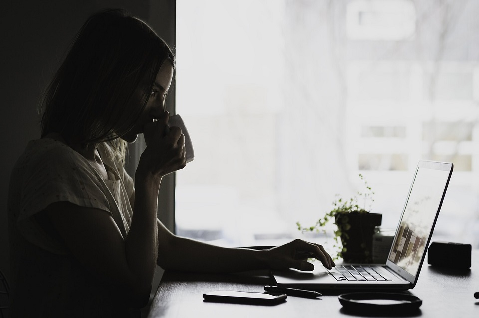 woman sipping coffee and typing on a laptop