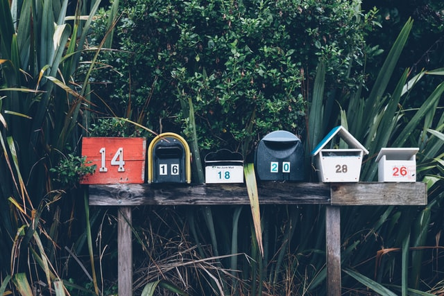 a series of mailboxes with different numbers on wooden posts