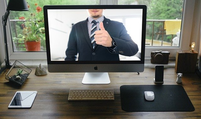 man in suit giving thumbs-up sign during video conference on PC
