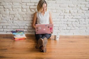 Woman sitting on floor with pink laptop